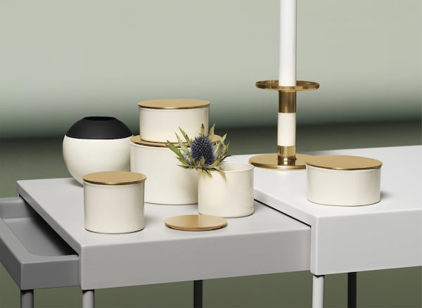 Boîtes, vases et bougeoir en couleur ivoire, noir et doré, présentés sur un ensemble de tables gigognes.