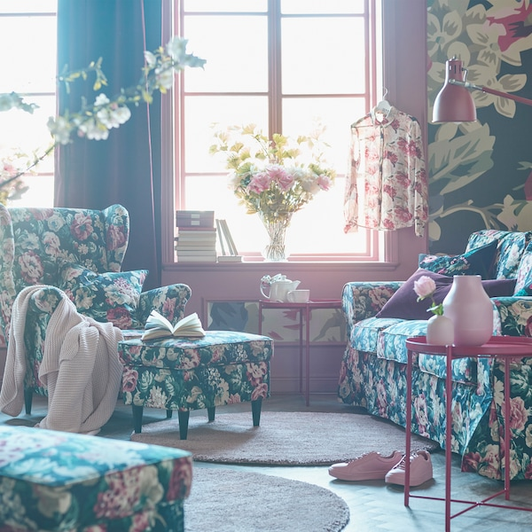 Bold floral patterned sofa, armchair, footstool and cushions in a living room with a bold floral patterned wallpaper.