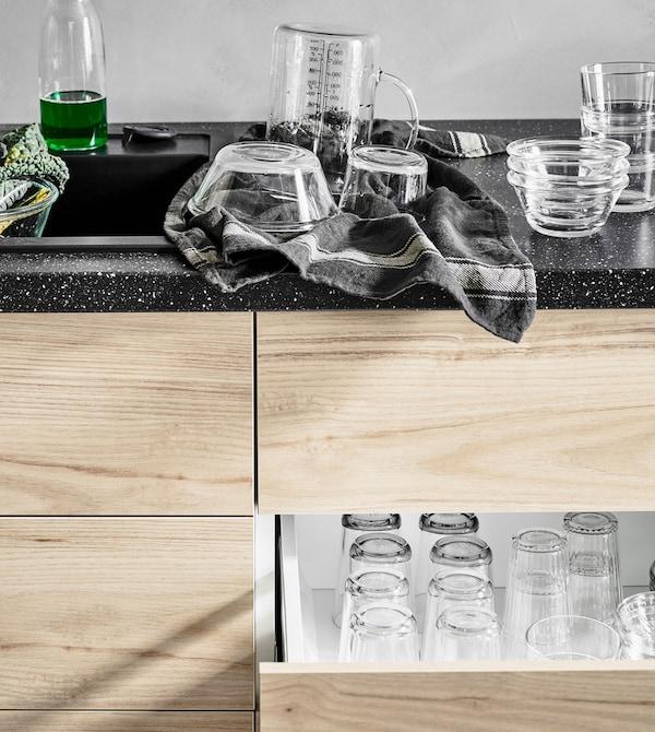 Bols en train d'être essuyés, sur un plan de travail, au-dessus d'un tiroir motif frêne ouvert où sont rangées des tasses en verre