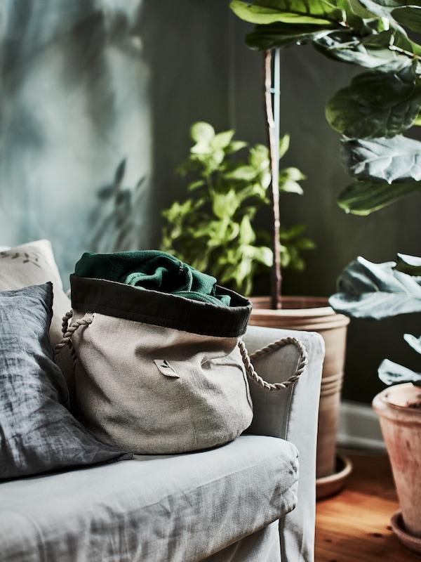 Bolsa de cultivo beige impermeable con asas rizadas de yute sobre un sofá gris junto a grandes plantas.