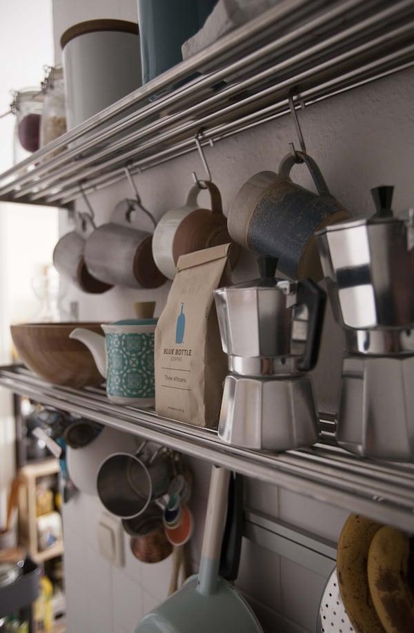 Bolsas de café, cafeteras y varias tazas y objetos en estanterías.