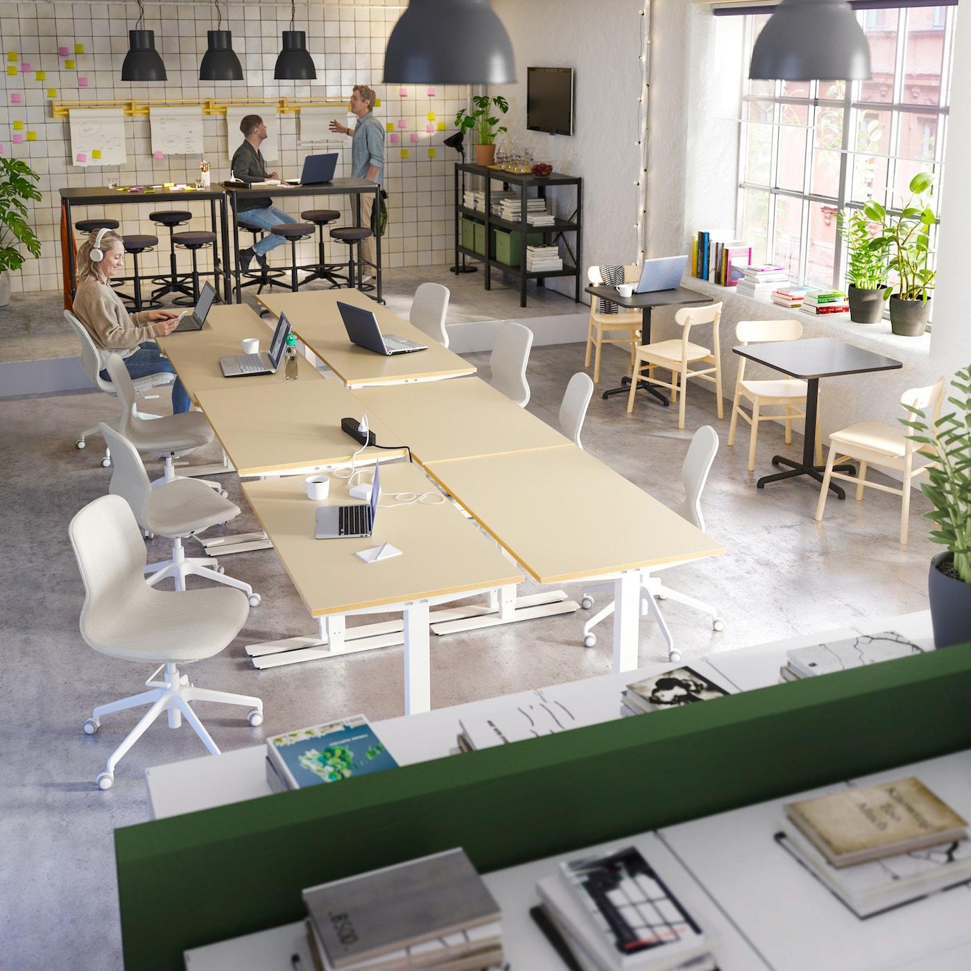 Большой офис с открытой планировкой, двое мужчин работают за высокими столами, за столом на белом стуле сидит женщина и пишет электронные письма.