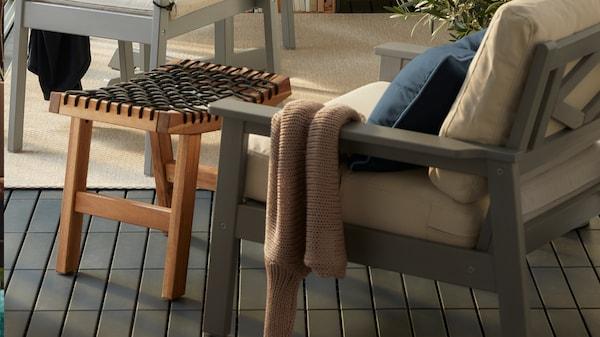 BONDHOLMEN serie på en skuggig altan med kuddar och plädar . På bordet står chips och iste framdukat.