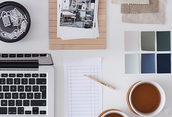 Book your online interior design service with our interior designer and home furnshing expersts. An image with a white desk workspace with a laptop, a notepad, a tea cup, pictures of a project living space, some fabric samples and colour samples.