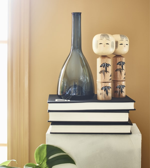 Books, a vase, and figurines sit on top of a pedestal.