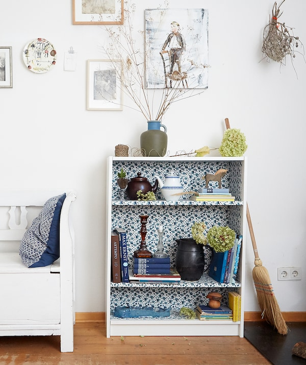Books and ornaments on a small bookcase with floral interior, in a room with white walls and wooden floor.