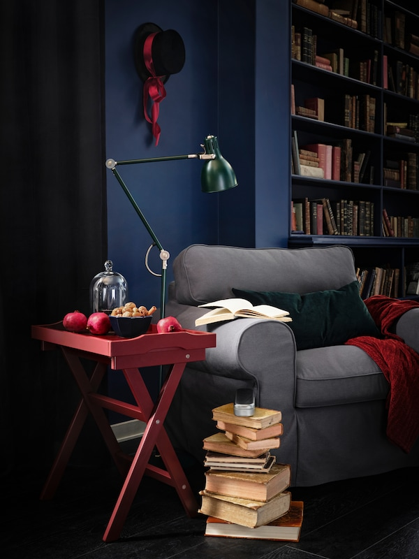 Books are piled up next to a cosy-looking EKTORP armchair with a red table and green lamp stood next to it.
