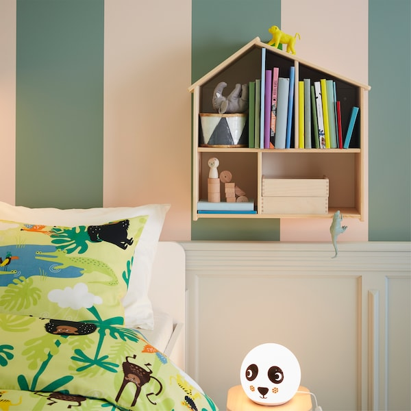 Books in a dollhouse mounted on a wall, jungle patterned bed textiles and a panda patterned table lamp.