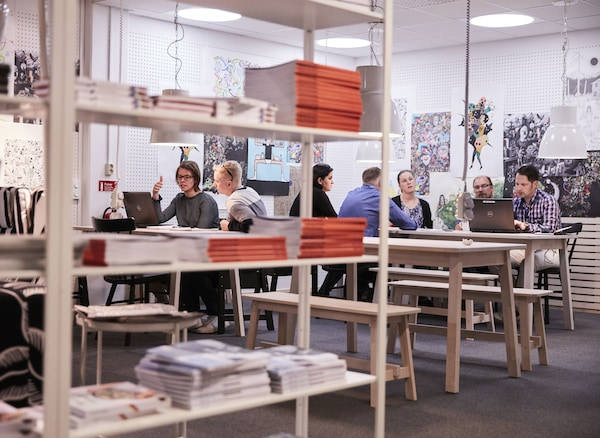Bookshelves, wall art and people working in groups on long tables.