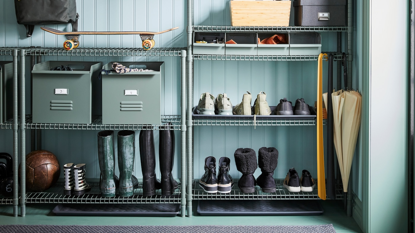 Boots, shoes, metal REJSA boxes, shoehorns, a skateboard and other items are stored on OMAR shelving in a hallway.