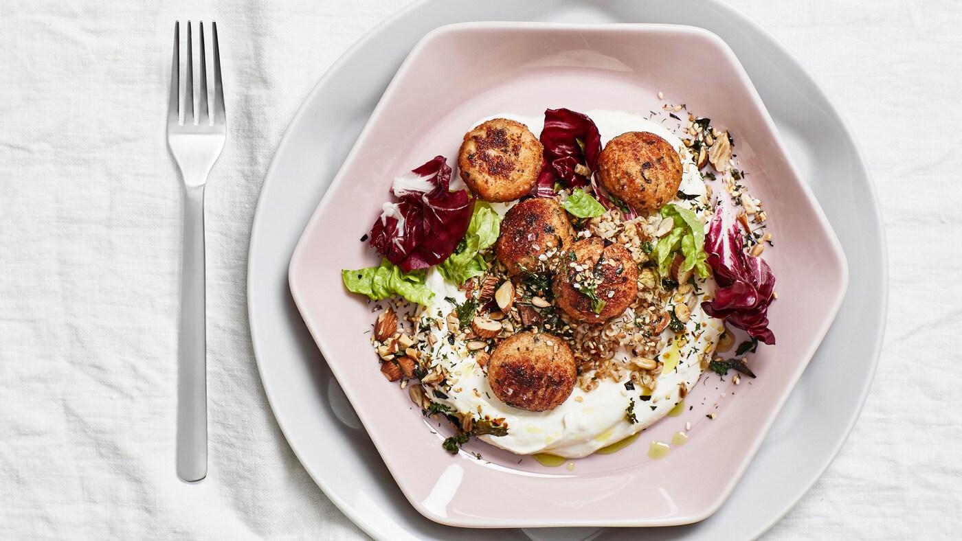 Bord dækket med en hvid dug, en gaffel og en sekskantet tallerken i støvet lyserød med 5 torskeboller, salat, nødder og yoghurt.