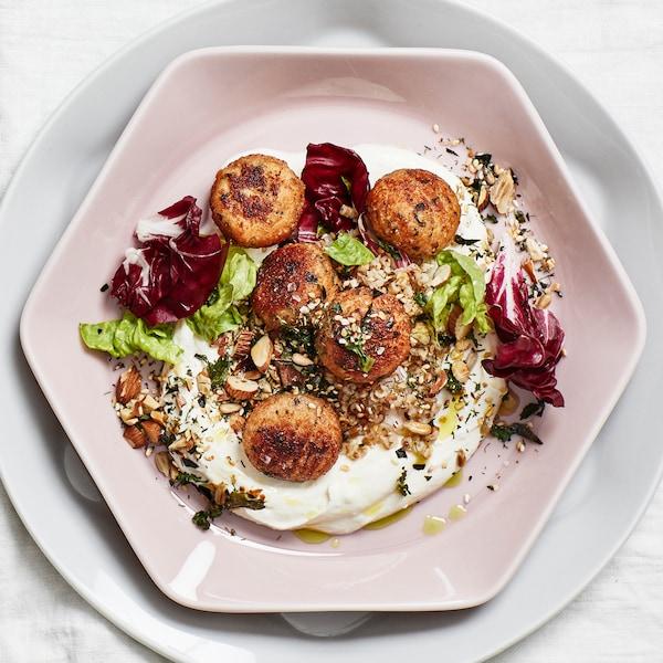 Bord dekket med hvit duk og en pudderrosa sekskantet tallerken med fem torskeboller, grønnsaker, nøtter og yoghurt.