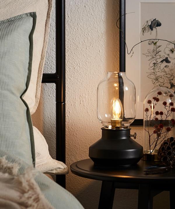 Bord d'un lit fait avec tête de lit haute, des oreillers qui y sont adossés; table de chevet ronde avec une lampe LED en forme de lampe à huile.