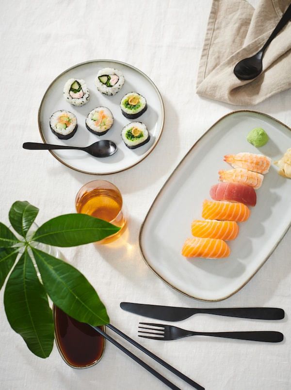 Bord med hvit duk, sushi servert på GLADELIG tallerkener, TILLAGD bestikk og en dekorativ kvist i et glass.