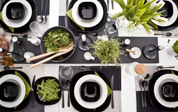 Borddækning i sort/hvid med stærke grønne kontrastfarver fra planter, mad og servietter.