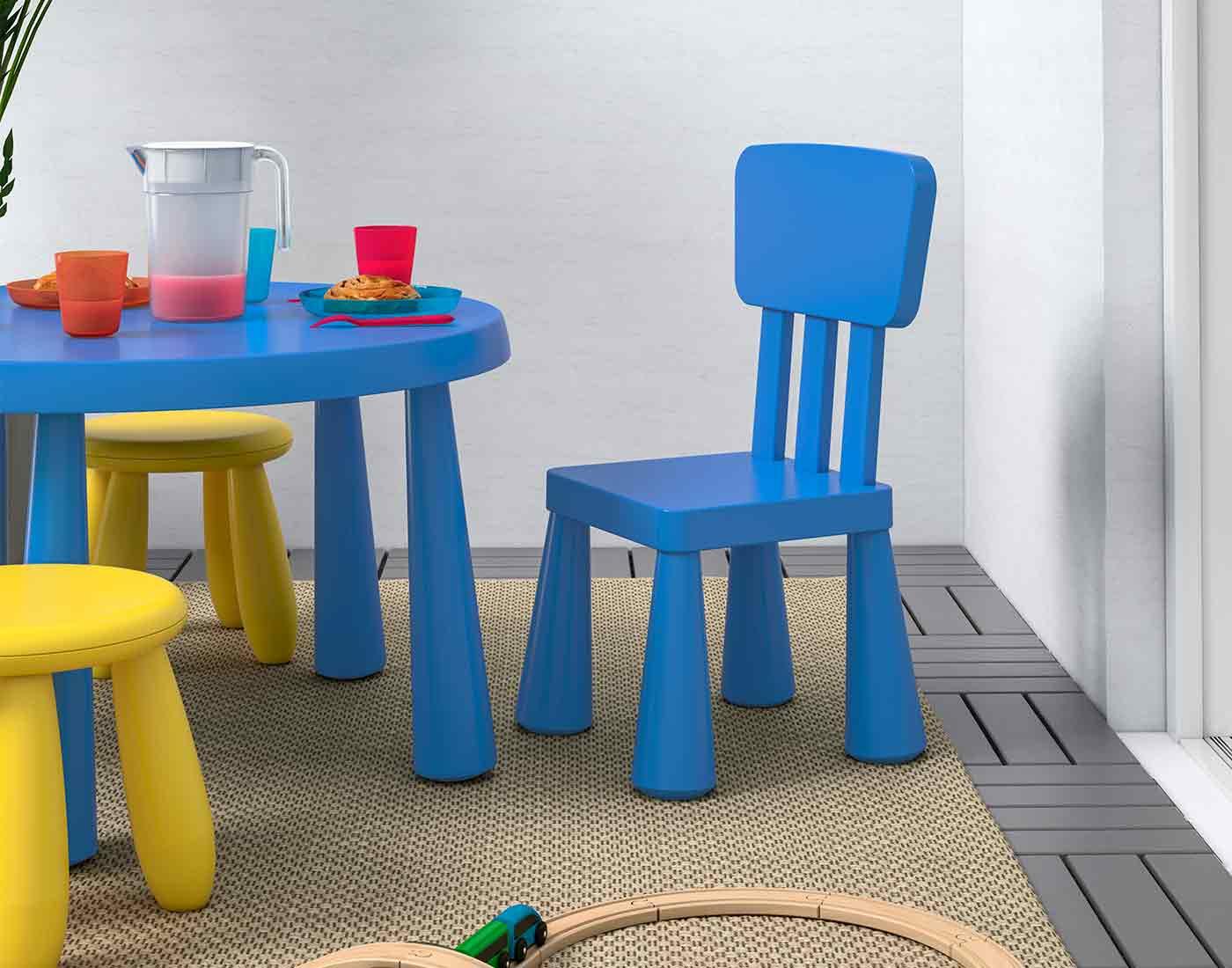 Børne havemøbler i blå og gul der står på en altan.
