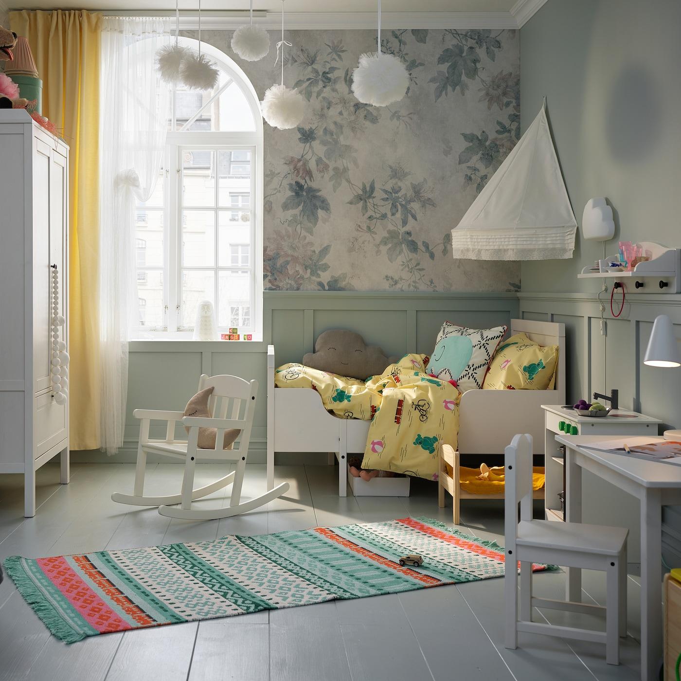 Børneværelse med en seng, en sengehimmel, et garderobeskab og et bord og en stol i hvidt. Farvestrålende tæppe ligger på tværs af gulvet.