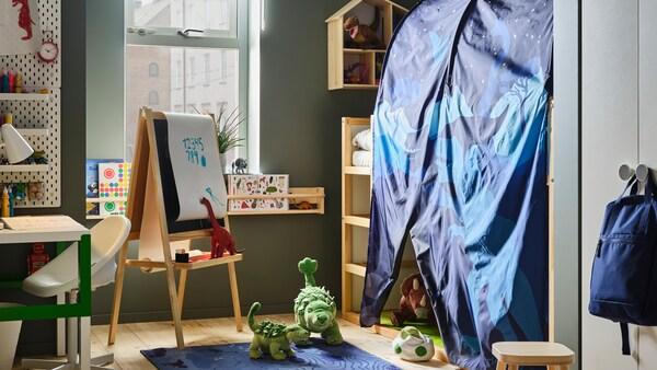 Børneværelse med et blåt sengetelt, dinosaurtøjdyr, et hvidt/grønt skrivebord og et blåt tæppe.