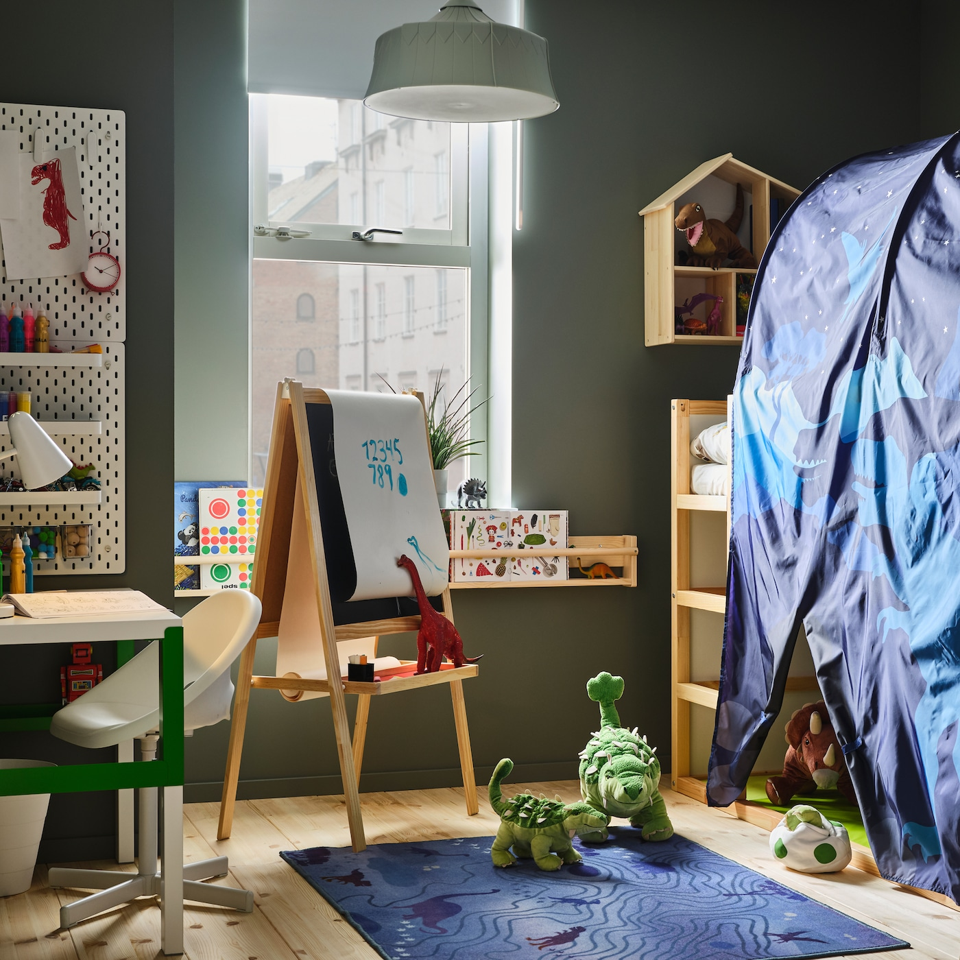 Børneværelse med et blåt sengetelt, dinosaurtøjdyr, et hvidt/grønt skrivebord, en lysegrøn loftlampe og et blåt tæppe.