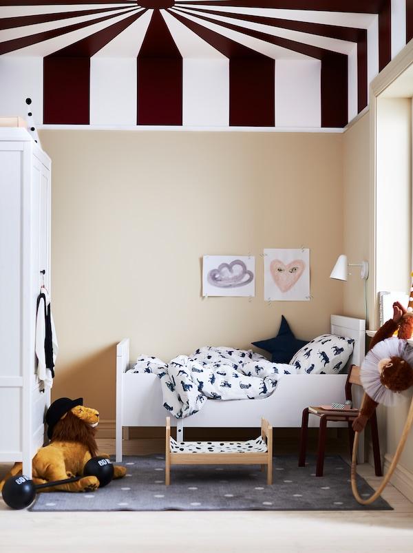 Børneværelse med et loft, der er malet som taget i et cirkustelt, en hvid SUNDVIK udtræksseng og hvidt og mørkeblåt sengetøj.