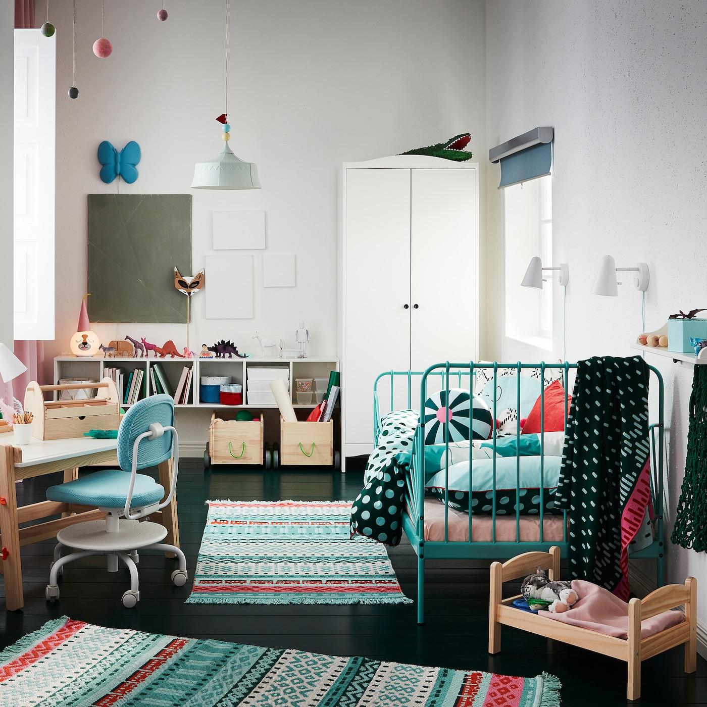Børneværelse med farvestrålende tæpper, et turkis sengestel, et hvidt garderobeskab, en dukkeseng og et skrivebord til børn.