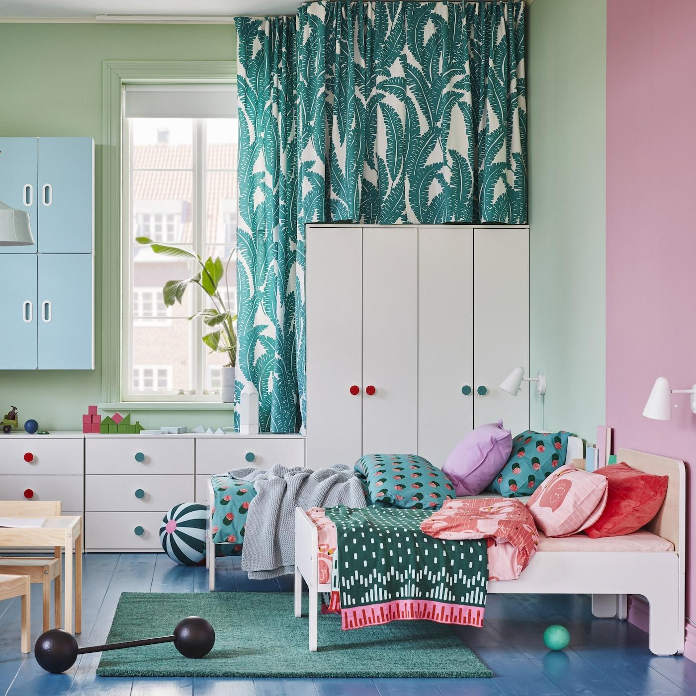 Børneværelse med hvide garderobeskabe og kommoder, 2 udtrækssenge, et grønt tæppe og blå vægskabe.