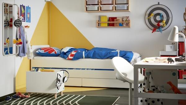 Børneværelse med hvide vægge med et grafisk gult mønster, en hvid seng med opbevaring nedenunder og blåt og rødt sengetøj.