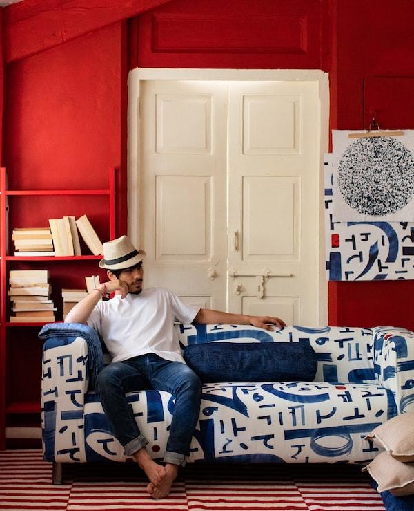 Bosonog čovek sa šeširom sedi na plavoj i beloj sofi u prostoriji s crvenim zidovima, policom, belim vratima i tepihom u dve nijanse.