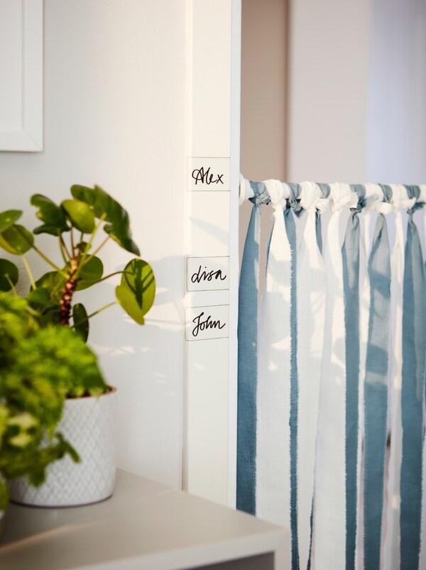 BOTAREN šipka za zavesu za tuširanje je okačena širom vrata. Duž vrata su IKEA 365+ etikete, a na svakoj je napisano ime.