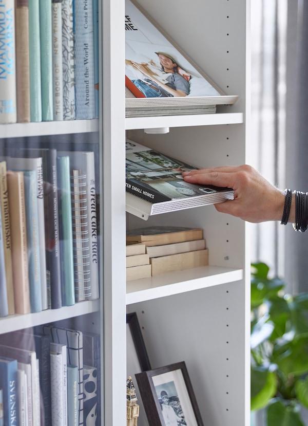 BOTTNA رفوف عرض شبكية من ايكيا بلون بيج فاتح مثبتة في خزانة BILLY بيضاء، تحتوي على كتب.