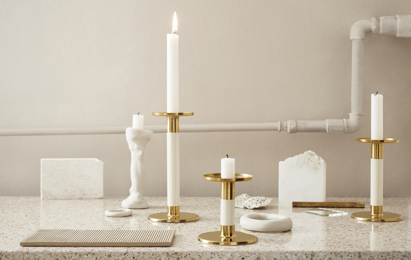 Bougeoirs couleur ivoire et doré présentés sur un plan de travail en marbre.