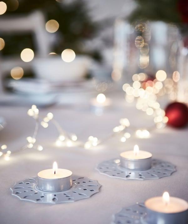 Bougies chauffe-plat sur bougeoirs décoratifs placés sur la table; en flou d'arrière-plan, une grande table dressée pour le repas de Noël.