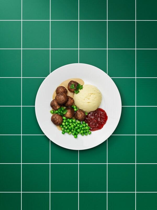 Boulettes à base de végétaux, sauce brune, purée de pommes de terre, confiture d'airelles, brocoli et brin de persil dans une assiette blanche toutesimple.