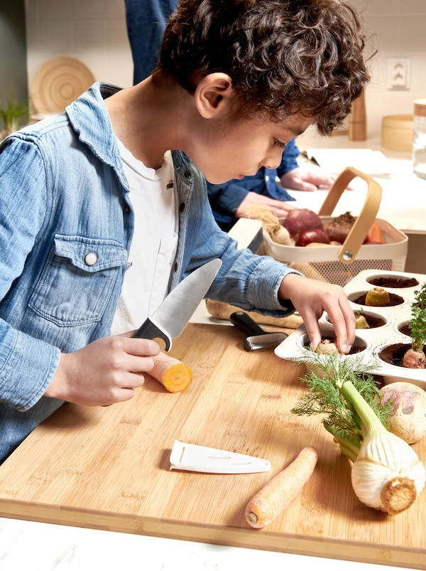 Boy holding a SMÅBIT knife, cutting odd vegetables on a chopping board, and setting pieces in soil in a VARDAGEN muffin tin.