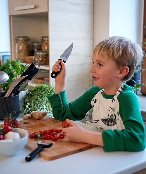Boy holds a black SMÅBIT knife up as he works at a PROPPMÄTT chopping board with sliced tomatoes and SMÅBIT peeler.