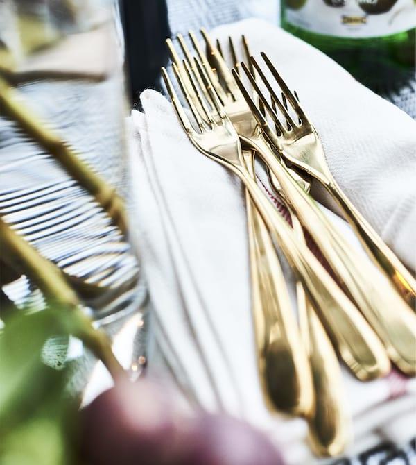 Brass coloured forks on a pile of napkins.