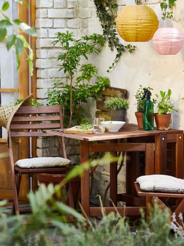 Braune Gartenöbel aus Holz mit grünen Pflanzen und bunten Außenlampen