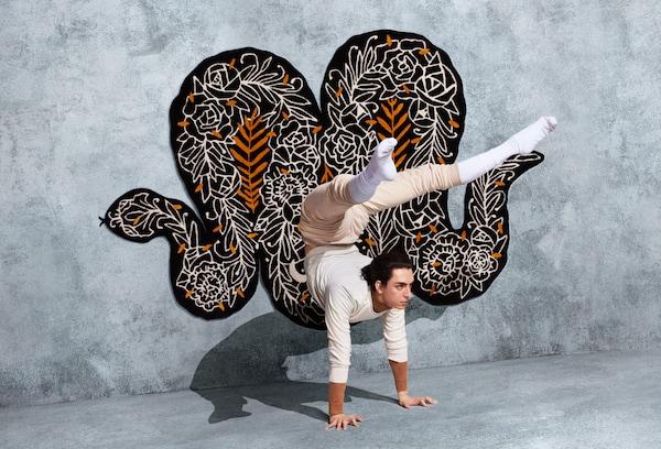 Brązowo-biało-pomarańczowy dywan w kształcie węża z motywem kwiatów, zaprojektowany przez Supakitch do kolekcji IKEA ART EVENT 2019.