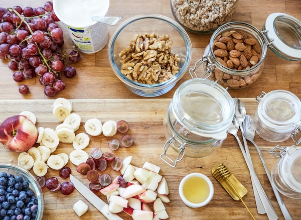 Breakfast ingredients, including chopped fruit, nuts and glass jars, laid out on a wooden countertop.