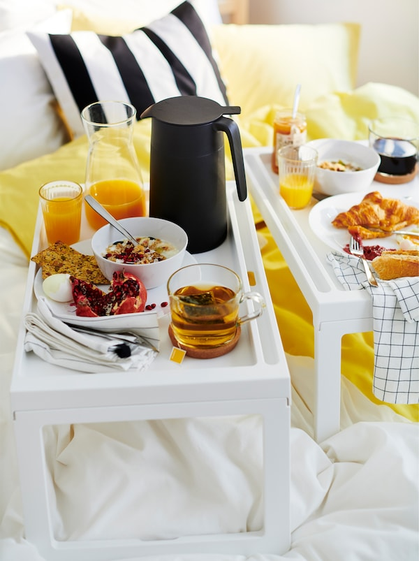 Breakfast – juice, croissants, muesli, coffee – served on two KLIPSK bed trays, placed atop a slightly dishevelled bed.