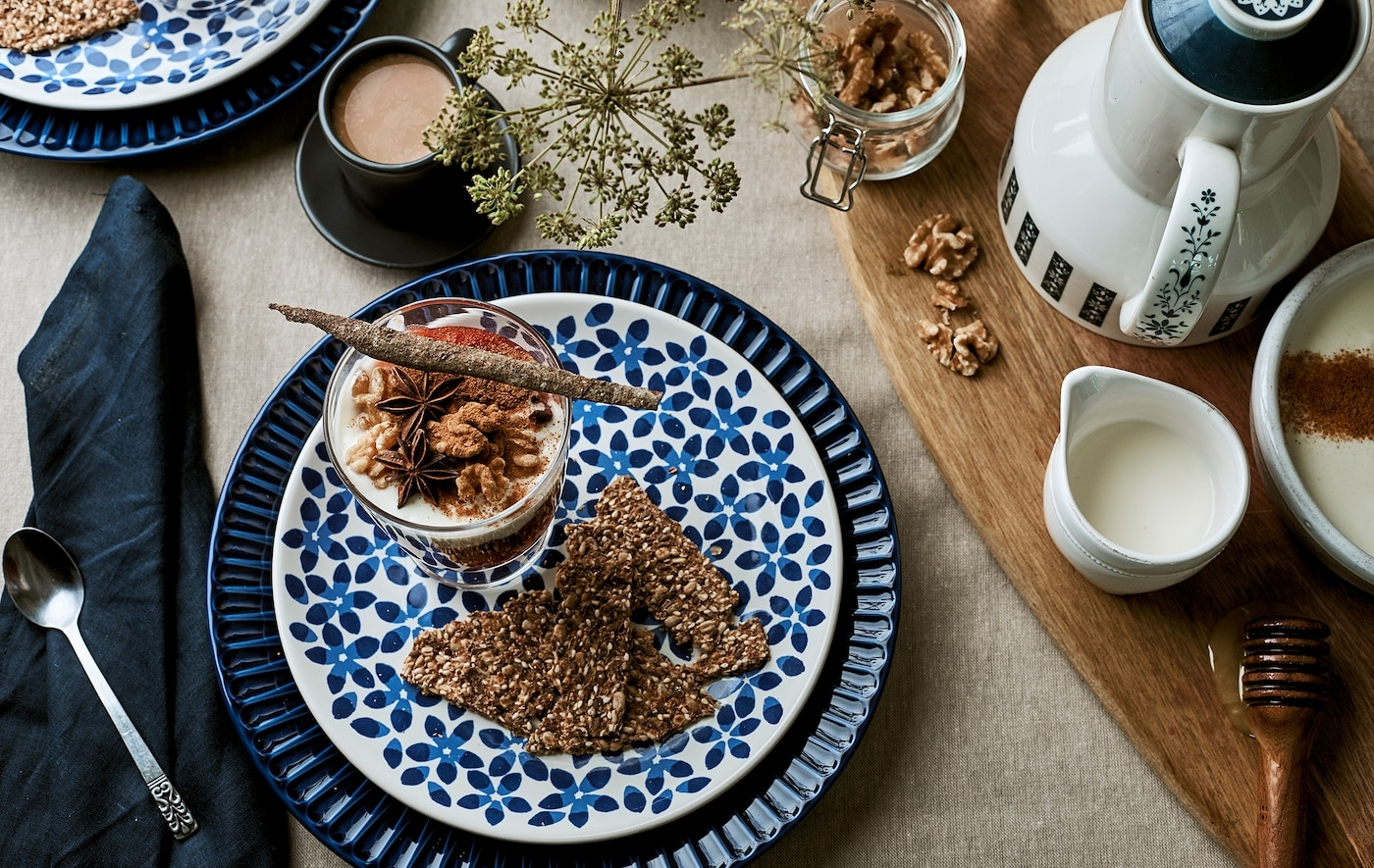 Breakfast table set with linen, patterned blue plates, granola in a glass and coffee accessories on a chopping board.