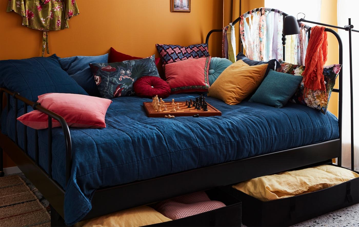 Bred seng redt med masser af farvestrålende puder og et skakbræt ovenpå. Sengetøj er opbevaret i sengeskuffer under sengen.