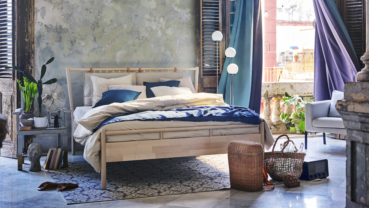 Březová postel s povlečením v béžové a modré, tyrkysové závěsy a světlo