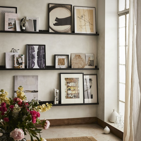 Bright, airy living room. 3 black picture ledges against wall across from floor length window. Collection of art in various sized black frames on picture ledges