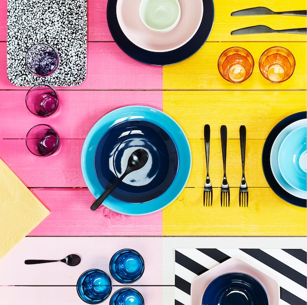 Bright, block-colored surface with a variety of colored bowls, cutlery and glasses laid out across it.