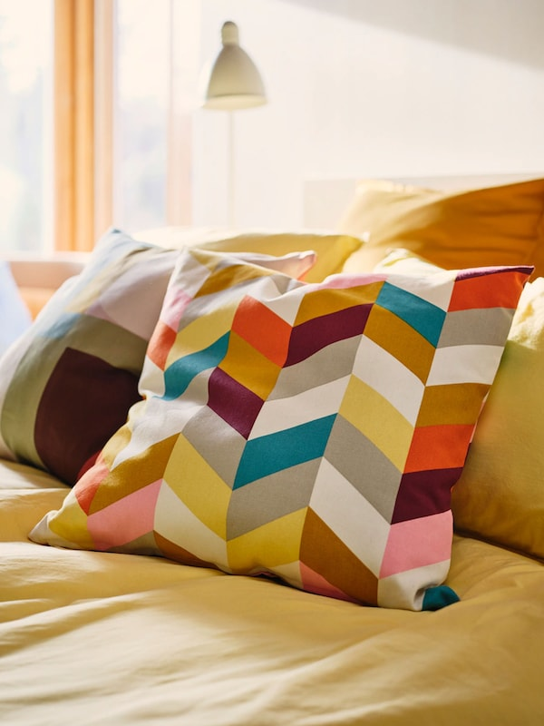Bright, colourful pillow sitting on yellow duvet