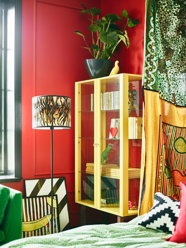 Bright green coloured furniture and red walls help make this stylist's dream bedroom come together.