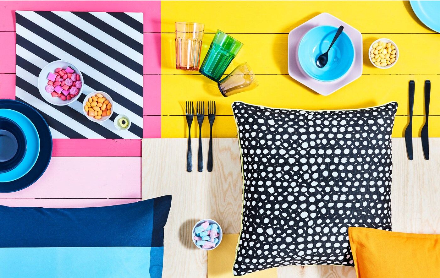 Brightly block-coloured surface with various tableware, bowls of candy and patterned cushions laid out on it.