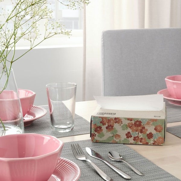 Brightly lit dining room. Pink dinnerware set with grey placemats