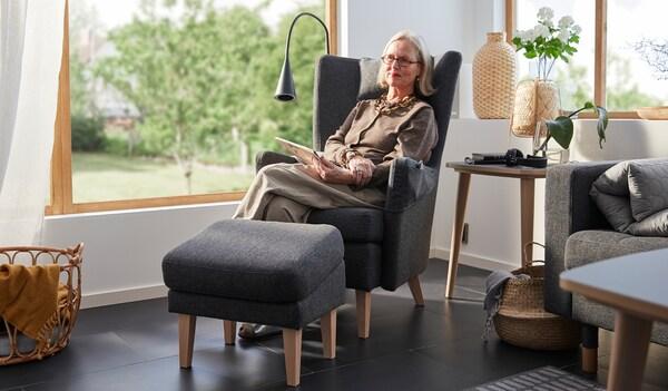 Britt Monti assise dans un fauteuil OMTÄNKSAM dans un coin ensoleillé d'une pièce avec de grandes fenêtres. Un jardin en toile de fond.
